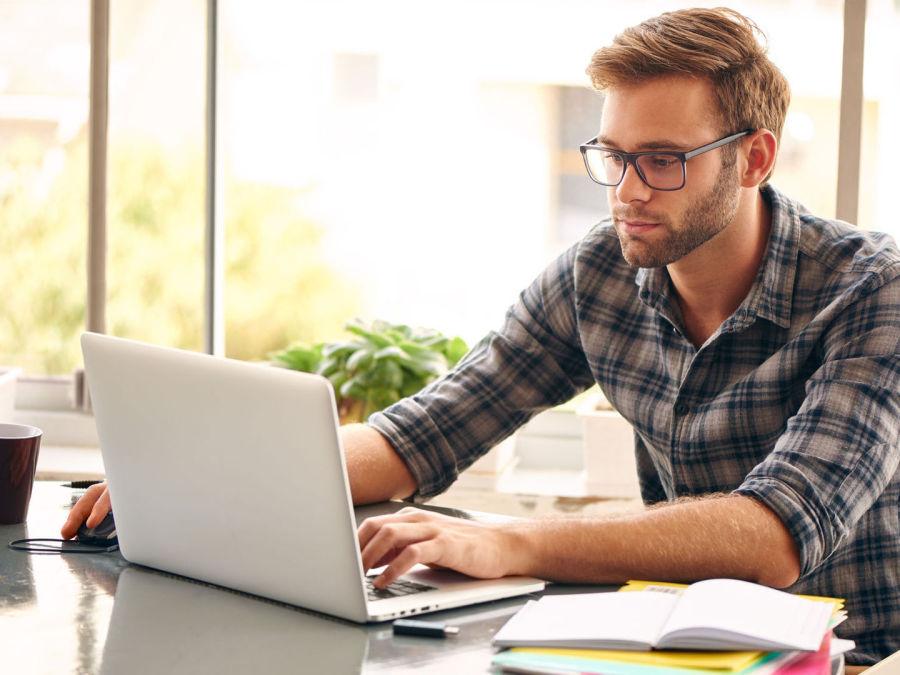 Mann mit Brille vor Laptop